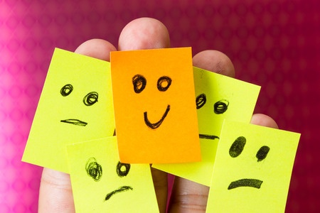 36378525 - concept for optimism with paper faces on multiple fingers one with a happy good attitude