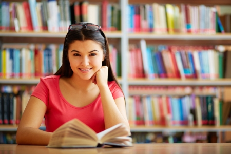 17534102 - portrait of cute girl with open book looking at camera in college library