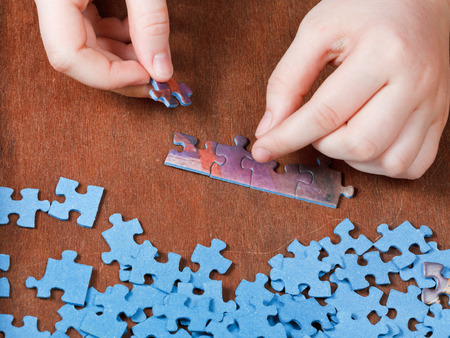 27484163 - fitting of jigsaw puzzles on wooden table