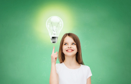 39596665 - education, energy saving, advertising and people concept - smiling little girl in white blank t-shirt pointing finger up to light bulb over green chalk board background