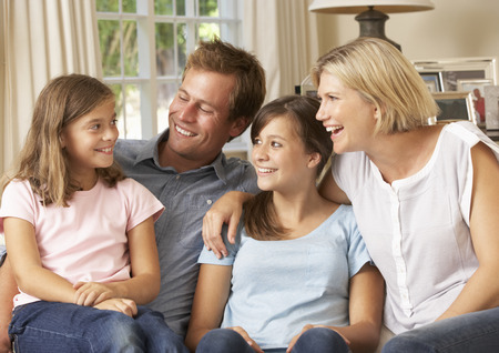 42163844 - family group sitting on sofa indoors