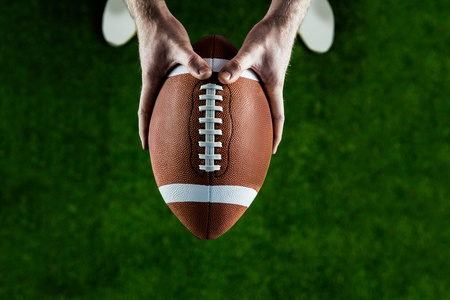 44459411 - american football player holding up football on american football field
